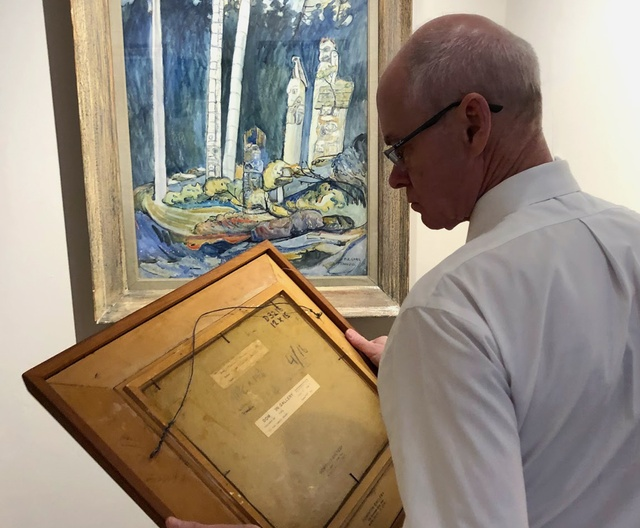 Alan Klinkhoff examining the back of a Lawren Harris painting with an Emily Carr watercolour hanging in the background.